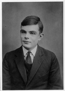 Alan Turing. This image is in the public domain in the US because its copyright has expired.